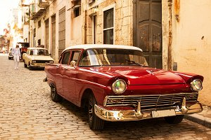 Red old and classical car in road of