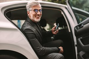 Smiling mature businessman in taxi