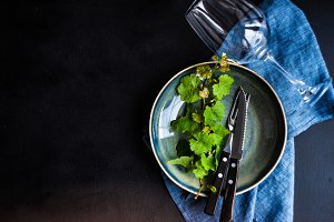 Dark table setting with grape vine