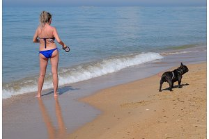 Woman with a dog on the beach by the