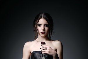 Beautiful goth girl holds rose