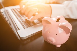 Piggy Bank Near Male Hands Typing on