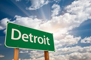 Detroit Green Road Sign Over Clouds