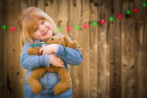 Girl Holding Teddy Bear In Front of