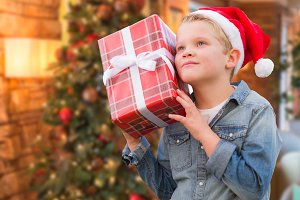 Boy Wearing Santa Hat Holding Christ