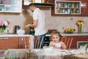 Little kid girl plays with flour whi