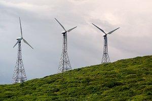 Wind turbine on the green hill in bl