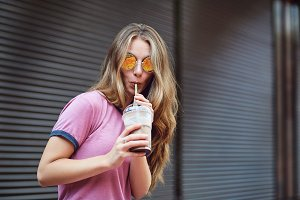 A blond hipster girl  drinks