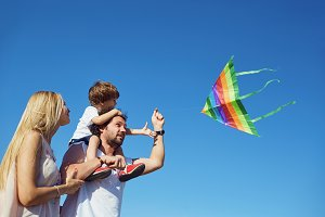 Family with a kite  on the field i