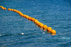 Orange buoys on a rope in the sea
