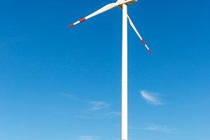white wind turbine with trees