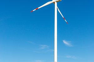 Big white wind turbine on tree line