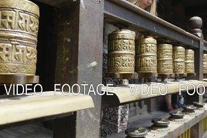 Woman spins prayer wheels in Patan