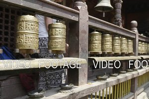 Woman spins prayer wheels in Patan