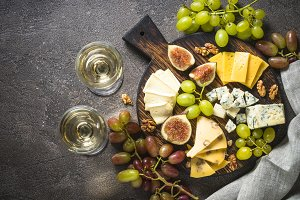 Cheese plate with grapes, figs and n