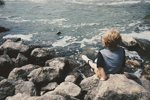 Boy Sitting on Rocks at River