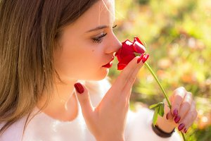 Girl sniffing a red rose in San Vale