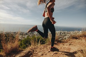 Young woman jogging on rocky path