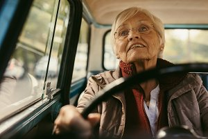Senior female driving a vintage car