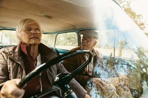 Senior couple traveling by car