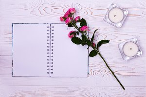 Blank notebook, flower, candles on a