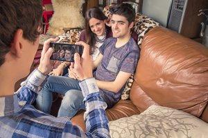 Friend taking photos to teen couple