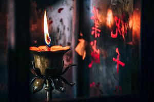 Burning Candle in Dark inside Shrine