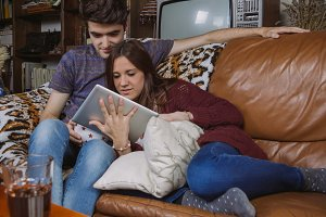 Young couple looking tablet on sofa