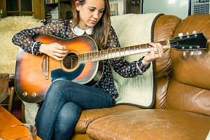 Hipster girl playing acoustic guitar