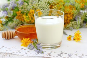 Glass of milk and flower honey in a