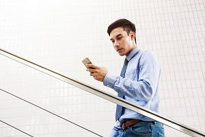 Young Asian businessman texting