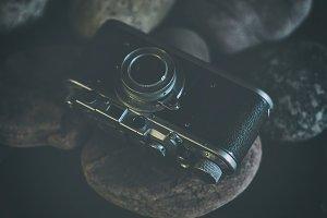 Vintage camera stands on stones