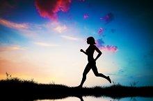 Silhouette of girl running at sunset