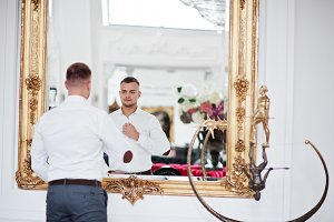 Fashionable man against mirror at wh