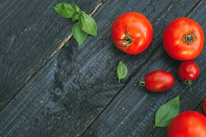 Red tomatoes on a wooden black backg
