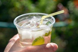 Lemonade in a plastic mug in hand cl