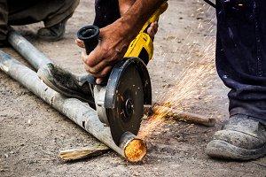 Worker cutting metal pipe