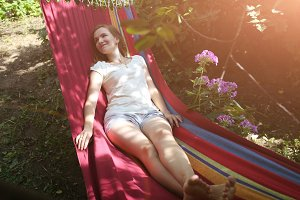 Girl lying in colourful hammock