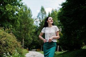 Brunette girl in green skirt and whi
