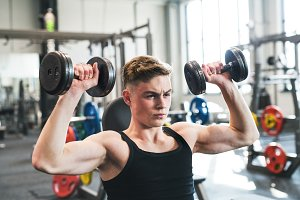 Young fit man in gym exercising with
