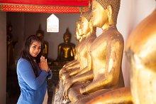 Woman worshiping Buddha in temple.