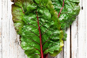 Swiss chard leaf on white wood
