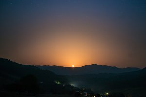 Moon rising on night sky