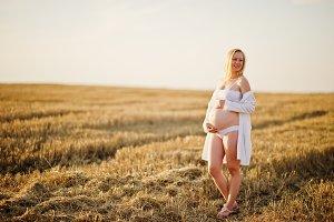 Blonde pregnant woman in wreath fiel
