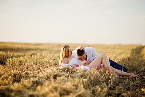 Pregnant couple in wreath field at w