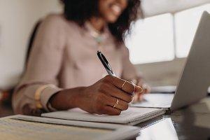 Woman making notes looking at laptop