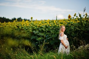 Blonde pregnant mother in sunflowers