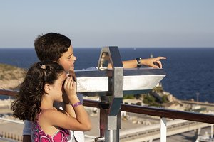 Boy and girl using a binoculars