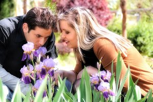 Young couple smelling a purple lilie