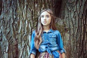 Beautiful girl standing at tree.
